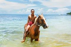 年轻人在海滩的骑乘马在塔韦乌尼岛海岛,斐济上 免版税库存照片