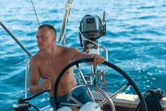 人在游艇担任船长在风帆种族期间在海 免版税库存照片