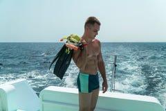 人在游艇的船尾的板条有飞翅的和一个面具在他的手上站立 人准备潜水在水下 免版税库存照片