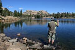 人在湖的用假蝇钓鱼 库存照片