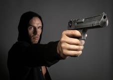 人在灰色背景隔绝的射击枪 免版税库存照片