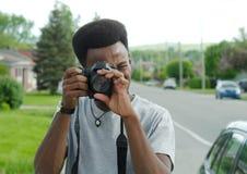 年轻人在照片写真之外的摄影师照相机 免版税库存图片