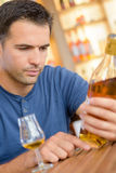 人在瓶白兰地酒的读书标签 图库摄影