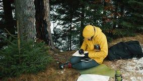 人在用雪盖的山冬天森林里采取笔记坐地面 影视素材