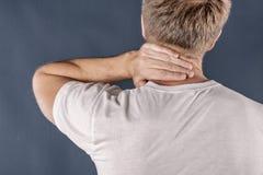 人在痛苦中的握他的脖子在蓝色背景 更低的脖子痛 接触他的痛苦的赤裸上身的人脖子 库存图片