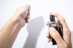人在白色使用一个详细的香水瓶 库存照片
