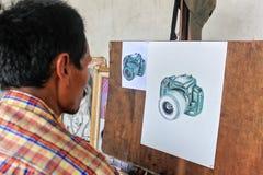 人在白色帆布的绘画照相机 库存照片