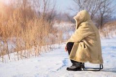 人在皮大衣坐多雪的平原 库存照片