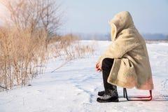 人在皮大衣坐多雪的平原 库存图片