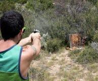 人在目标的射击手枪与壳在天空中 免版税图库摄影