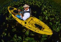 人在睡莲叶的皮船渔 免版税库存照片