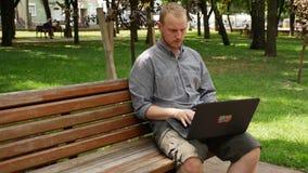 人在研究膝上型计算机的公园 股票录像