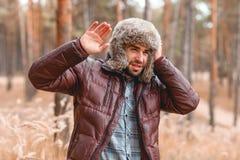 人在秋天森林里拿着一个帽子并且从风是闭合的 库存照片