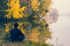 人在秋天湖之前 图库摄影
