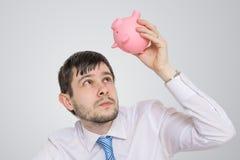 年轻人在空的贪心金钱银行看 免版税图库摄影