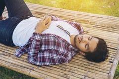 年轻人在竹床或位子上的作为休息 免版税库存照片