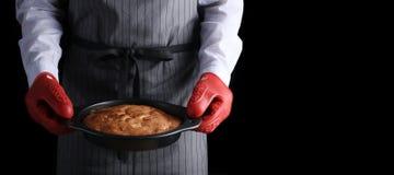人在红色握持热锅的布垫子藏品饼黑暗的背景中和隔绝在黑色 与成份的食谱概念在桌上 库存图片