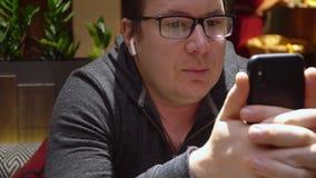 人在网上做视频通话使用电话和在餐馆博客作者自由职业者的无线earpnones 股票视频