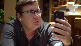 人在网上做视频通话使用电话和在餐馆博客作者自由职业者的无线earpnones 影视素材