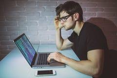 年轻人在膝上型计算机的programer工作夜和乱砍网络 年轻黑客攻击一个网络夜 免版税图库摄影