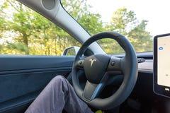 人在自动驾驶仪方式下的驾驶一个新的特斯拉模型3 图库摄影