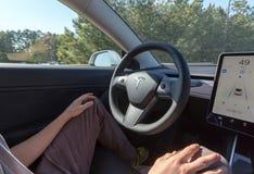人在自动驾驶仪方式下的驾驶一个新的特斯拉模型3 免版税库存照片