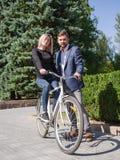 人在自行车乘坐他的女孩 库存图片