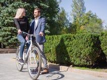 人在自行车乘坐他的女孩 免版税库存照片