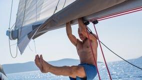年轻人在航行游艇的帆柱的手上拉扯了 体育运动 库存照片