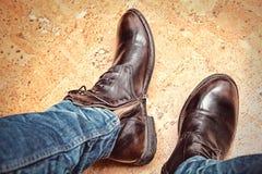 人在蓝色牛仔裤和棕色皮靴的时尚腿 免版税库存图片