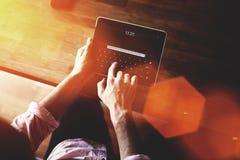 人在触摸板的正文消息的播种的图象,当坐在现代内部时的木桌上 免版税图库摄影