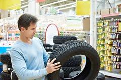 人在超级市场选择冬天汽车的散布的轮胎 免版税库存照片