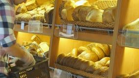 人在超级市场选择和放一个新鲜面包大面包入一个包裹 采取一个面包从的年轻人 股票录像