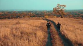 人在路生活方式道路冒险游客旅行本质上秋天去 慢动作录影 两徒步旅行者与 股票录像