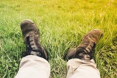 人在远足裤子的光的` s脚和肮脏在尘土黑色trekkin 免版税库存照片