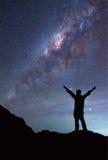 人在银河星系旁边站立 免版税库存照片