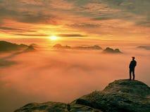 人在锋利的岩石峰顶的剪影逗留 满足远足者享受看法 岩石峭壁的高人 免版税库存图片