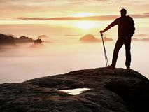 人在锋利的岩石峰顶的剪影逗留 满足远足者享受看法 岩石峭壁的高人 图库摄影