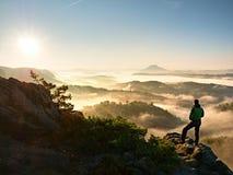 人在锋利的岩石峰顶的剪影逗留 满足远足者享受看法 免版税库存照片