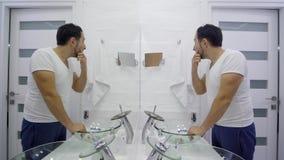 人在镜子前面洗涤  一件白色T恤杉的疲乏的不剃须的人 影视素材