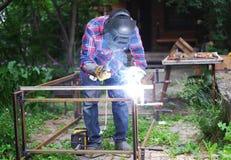 人在防毒面具焊接金属建筑房子外在一个夏日 免版税库存照片