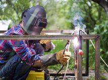人在防毒面具焊接金属建筑房子外在一个夏日 库存照片