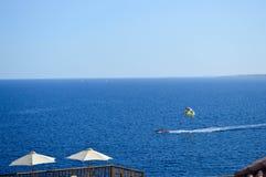 人在降伞参与帆伞运动,飞行高速被栓对一条小船在水海上一种温暖的热带手段的 免版税库存图片