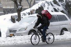 人在雪风暴的自行车做交付 免版税库存图片