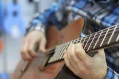 人在音乐商店,一种音乐心情,古典音乐弹一把古典吉他 免版税库存图片