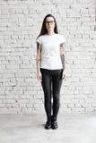 年轻人在顶楼刺字了穿空白的T恤杉的妇女,站立在砖墙前面 免版税图库摄影