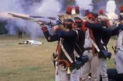 人在18世纪美国军用服装火步枪穿戴了在新的风举行的革命战争争斗再制定期间 免版税库存照片
