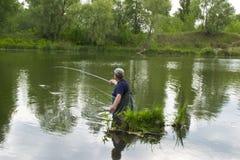 人在水中钓鱼 库存照片