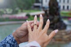 人在他可爱的女孩的手指上把圆环放 免版税图库摄影