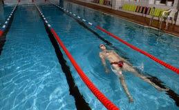 年轻人在水在游泳池说谎并且放松。 图库摄影